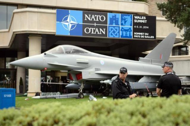 The NATO summit meeting--Police officers stands guard near to a model of Typhoon fighter jet at the Celtic Manor Hotel in Newport, South Wales (Picture: LEON NEAL/AFP/Getty Images)